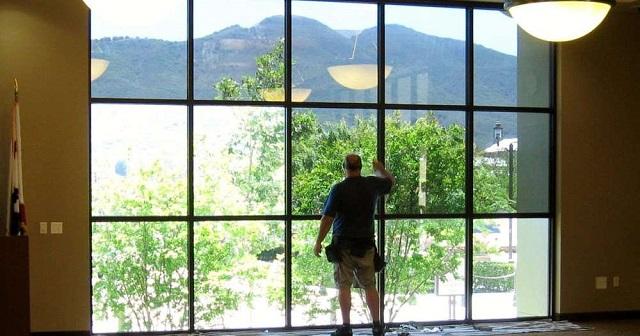 Thi công dá giấy chống nắng ở mặt kính bên trong công trình.